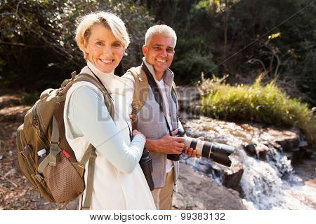 cheerful middle aged hikers relaxing by river enjoying outdoor activity