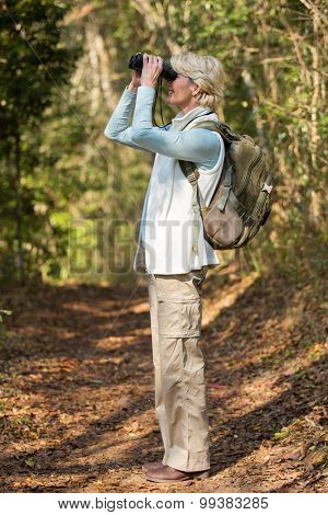 side view of mid age woman using binoculars bird watching in forest