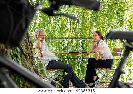 Younger And Older Business Woman Sitting In A Beer Garden