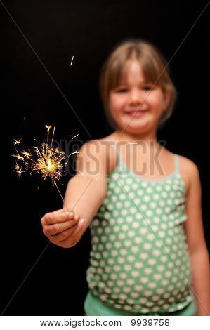 girl holding yellow sparkler firework with her hand and smiling