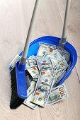 Broom sweeping dollars in scoop from on wooden floor, closeup poster