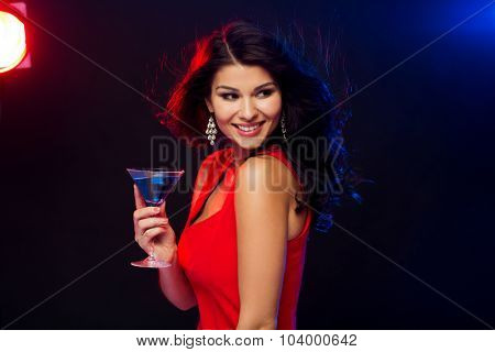 people, holidays, party, alcohol and leisure concept - beautiful sexy woman in red dress with cocktail glass at night club