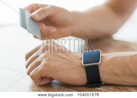 business, technology, cash free and internet people concept - close up of male hands with smart watch and credit card at office