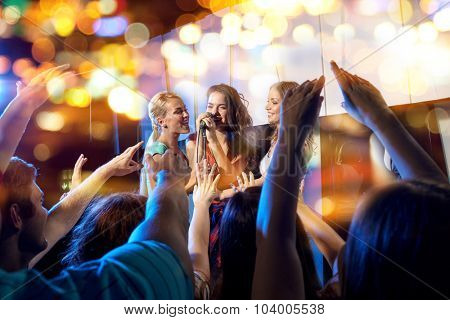 party, holidays, celebration, nightlife and people concept - happy young women singing karaoke in night club behind crowd of music fan