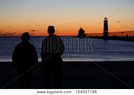 Couple watching sunset at lighthouse