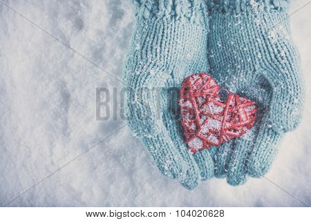 Woman hands in light teal knitted mittens are holding a beautiful glossy red heart in a snow winter background. Love and St. Valentine concept.