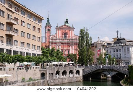 LJUBLJANA, SLOVENIA - JUN 30: Franciscan Church of the Annunciation and Triple Bridge on the Ljubljanica River in Ljubljana, Slovenia on Jun 30, 2015