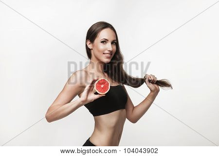 Portrait Of Young Fit Woman Holding Pink Grapefruit