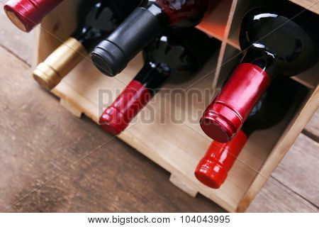 Box with wine bottlenecks on the table, close up.