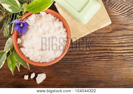 Aromatic bath salt in a clay cup and soap on a wooden background poster