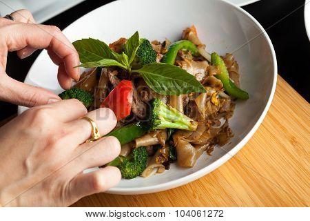 Food Stylist Garnishing a Dish