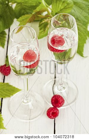 Two glasses of Himbeergeist schnaps with fruits and leaves on rustic table