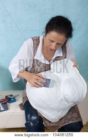 Woman sanding a plaster pregnancy belly cast with sanding paper