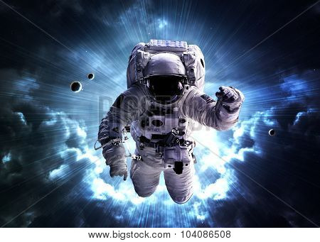 An astronaut floats above billions of stars. Stars provide the background. Elements of this Image Fu