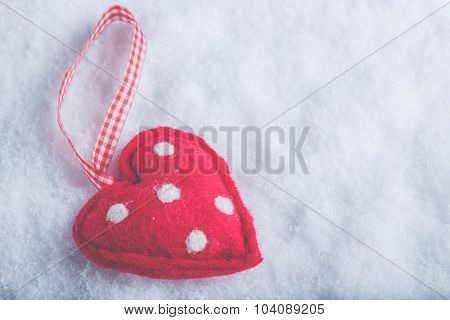 Red toy suave heart on a frosty white snow winter background. Love and St. Valentine concept.