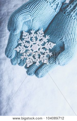 Female hands in light teal knitted mittens with sparkling wonderful snowflake on a white snow background. Winter and Christmas cozy concept.