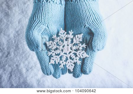 Female hands in light teal knitted mittens with sparkling wonderful snowflake on a white snow background. Winter and Christmas cozy concept. poster