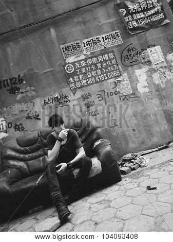 Guy Sitting in a Grungy Environment