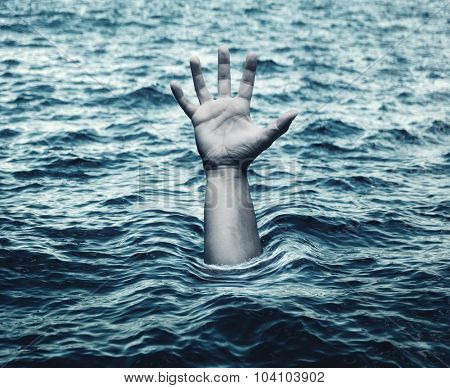 Hand of drowning man in sea