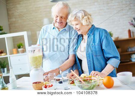 Happy seniors cooking fruit smoothie