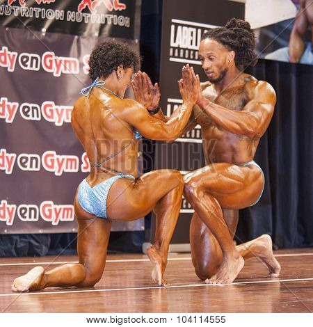 Bodybuilding Duo Holding Hands On The Knees On Stage