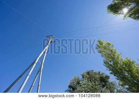 Railway catenary against a blue sky and sun