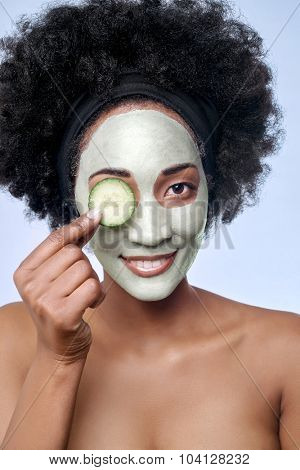 Portrait of beautiful black african model with a facial face mask holding a cucumber slice to her eye, rejuvenating skin care regime treatment beauty concept