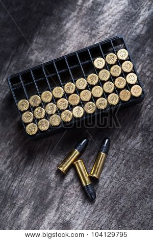 Scattering of small caliber cartridges on a wooden background. Other cartridges cartridges lies in capsules up. The picture from the top point. poster