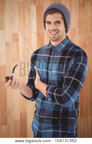 Portrait of happy man holding smoking pipe while standing against wooden wall