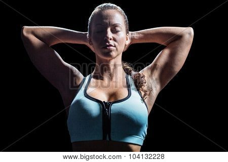 Sporty woman relaxing with hands behind head against black background poster