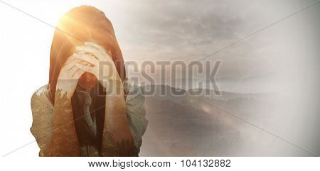 Troubled woman crying against trees and mountain range against cloudy sky