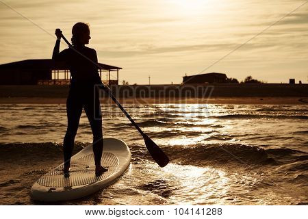 Silhouette Of Young Girl Paddleboarding At Sunset, Recreation Sport Paddling Ocean Beach Surf Orange