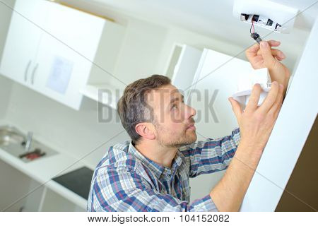 Fitting a smoke alarm in his home
