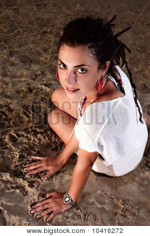 Girl in white dress and dreadlocks on sand