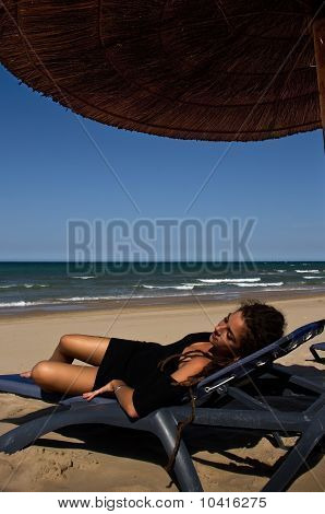 Girl in black dress relaxing on the beach
