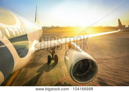 Airplane At Terminal Gate Ready For Takeoff - Modern International Airport During Sunset