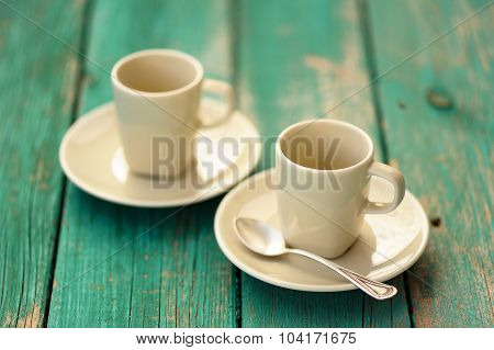 Two Empty Ebony Espresso Cups With Silver Spoon On Turquoise Shabby Background