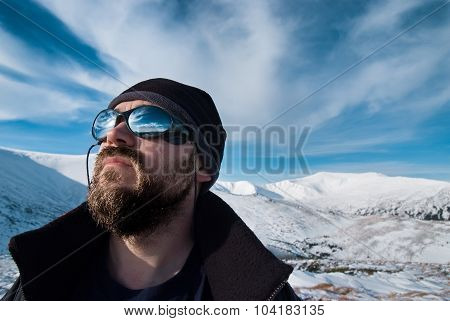 Portrait of a man with glasses and a beard in the snowy mountains