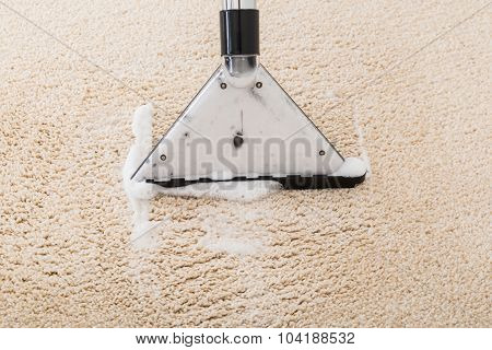 Close-up Of Vacuum Cleaner With Foam Over Wet Carpet poster