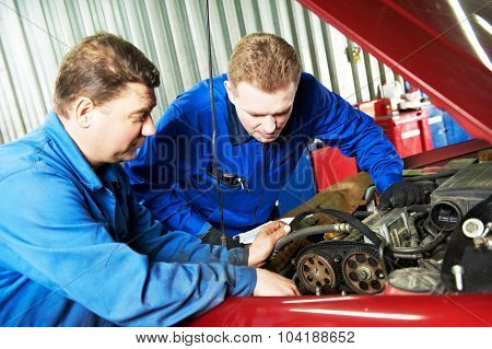 two motor mechanic engineers examining timing belt and internal combustion engine of automobile car at repair service station poster
