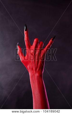 Scary devilish hand showing heavy metal gesture, studio shot on smoky background