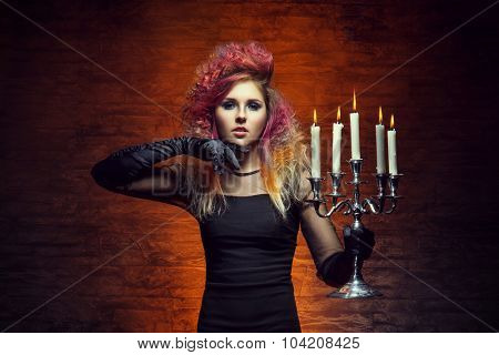 Young and beautiful witch making a witchcraft in dungeon. Halloween composition.