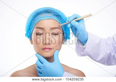 Doctor drawing perforation lines on face of patient before surgery poster