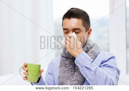 healthcare, flu, people, rhinitis and medicine concept - ill man blowing his nose with paper napkin and drinking tea at home