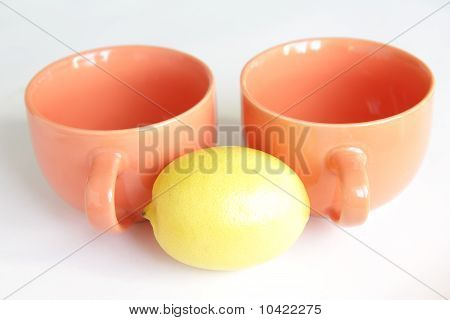 Two orange empty tea cups with lemon on white background