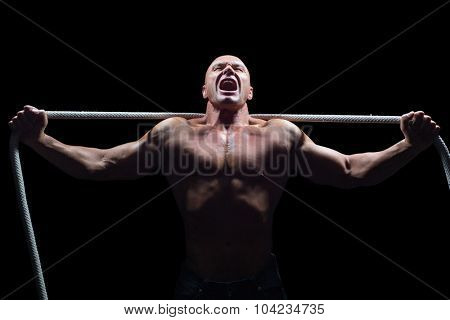 Aggressive man with arms outstretched holding rope against black background poster