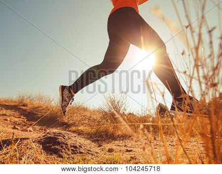 a female jogger sprinting down a grassy hill during sunrise or sunset on the hills above a city toned with a retro vintage instagram filter app or action effect - healthy jogging or running concept