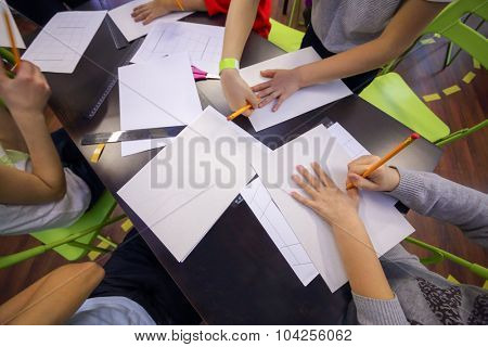 children encircle hand with a pencil on a sheet of paper
