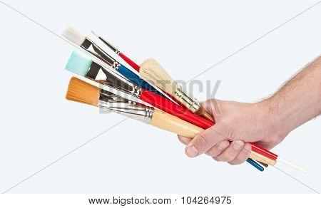 hand holding several brushes