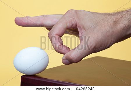 Hand about to flick an egg